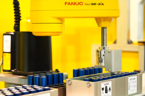 fanuc yellow robot packaging batteries